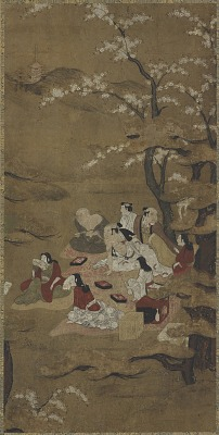 A picnic party: eight people seated under blossoming trees