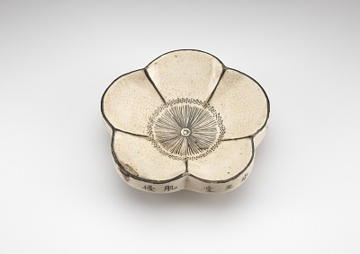 Saucer in form of plum blossom, with Chinese poem on rim and Chinese character written in lacquer on base