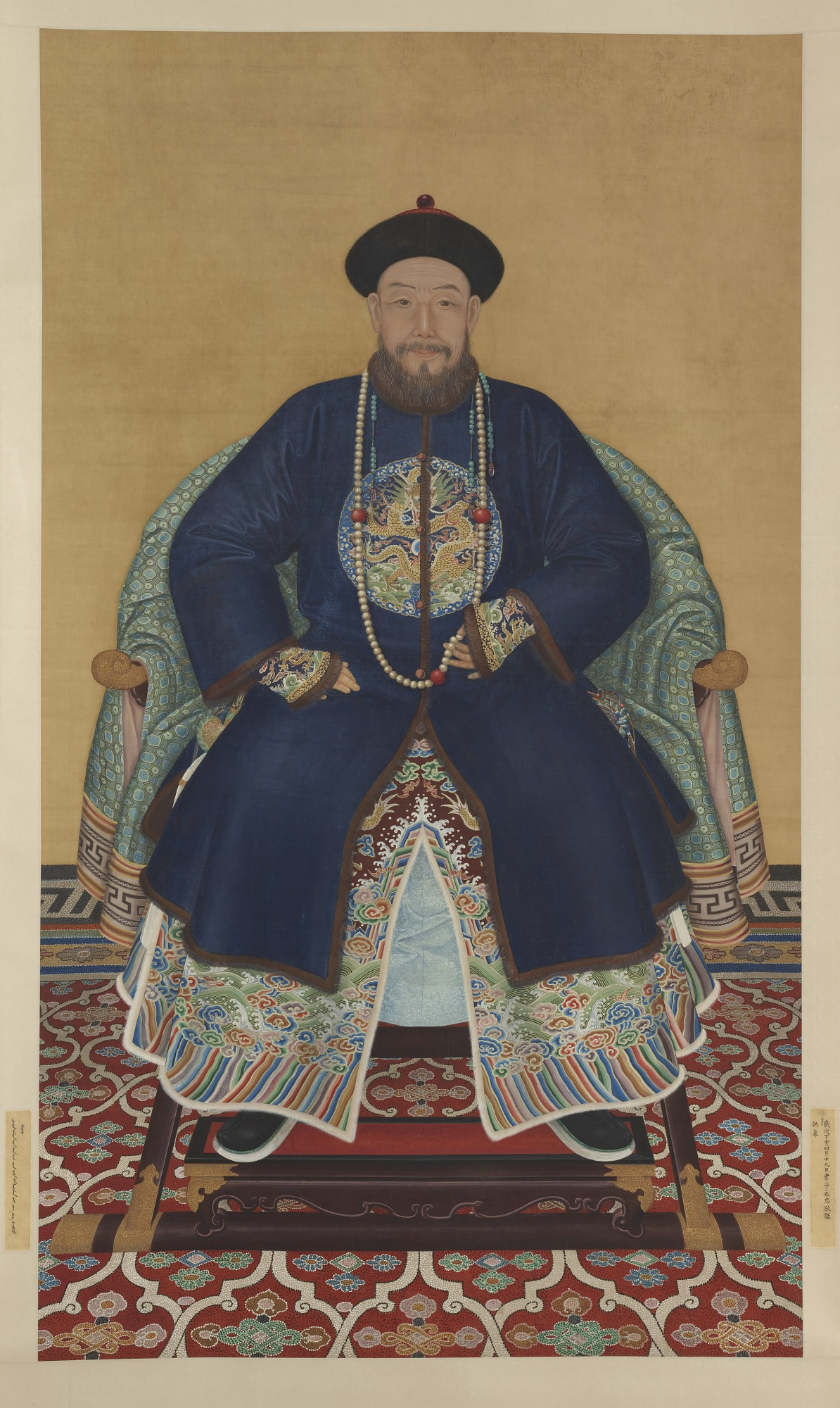 Ancestor portrait of Prince Hongming, dressed in a blue robe decorated with a dragon roundel on the chest, he wears a string of beads and holds a few beads between his fingers, he has a rounded beard and wears a black and red hat, seated on a light green patterned fabric draped chair, on a red and white patterned carpet