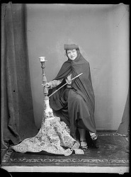 Studio Portrait: Western Woman in Studio Posed with Chador and Hookah [graphic]