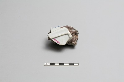 Fragment (part of foot and rim) fused to chunk of kiln debris