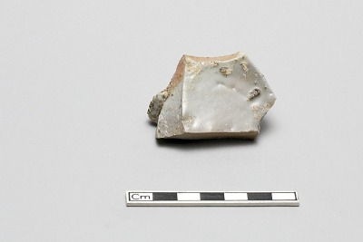 Base sherd of bowl, kiln waster, kiln grit attached, one edge has melted appearance