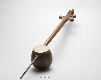 Muscial instrument (oriental lute, tar) with 3 strings and reddish wooden cocoanut-shaped sounding-box covered with parchment. Wood stem section with 3 hooks for metal strings.