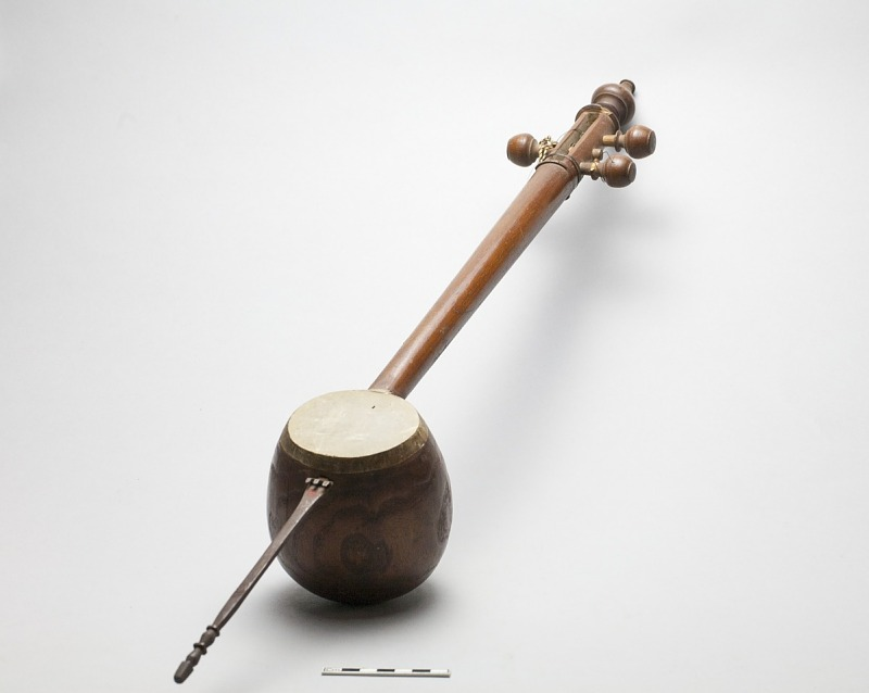 Image for Muscial instrument (oriental lute, tar) with 3 strings and reddish wooden cocoanut-shaped sounding-box covered with parchment. Wood stem section with 3 hooks for metal strings.