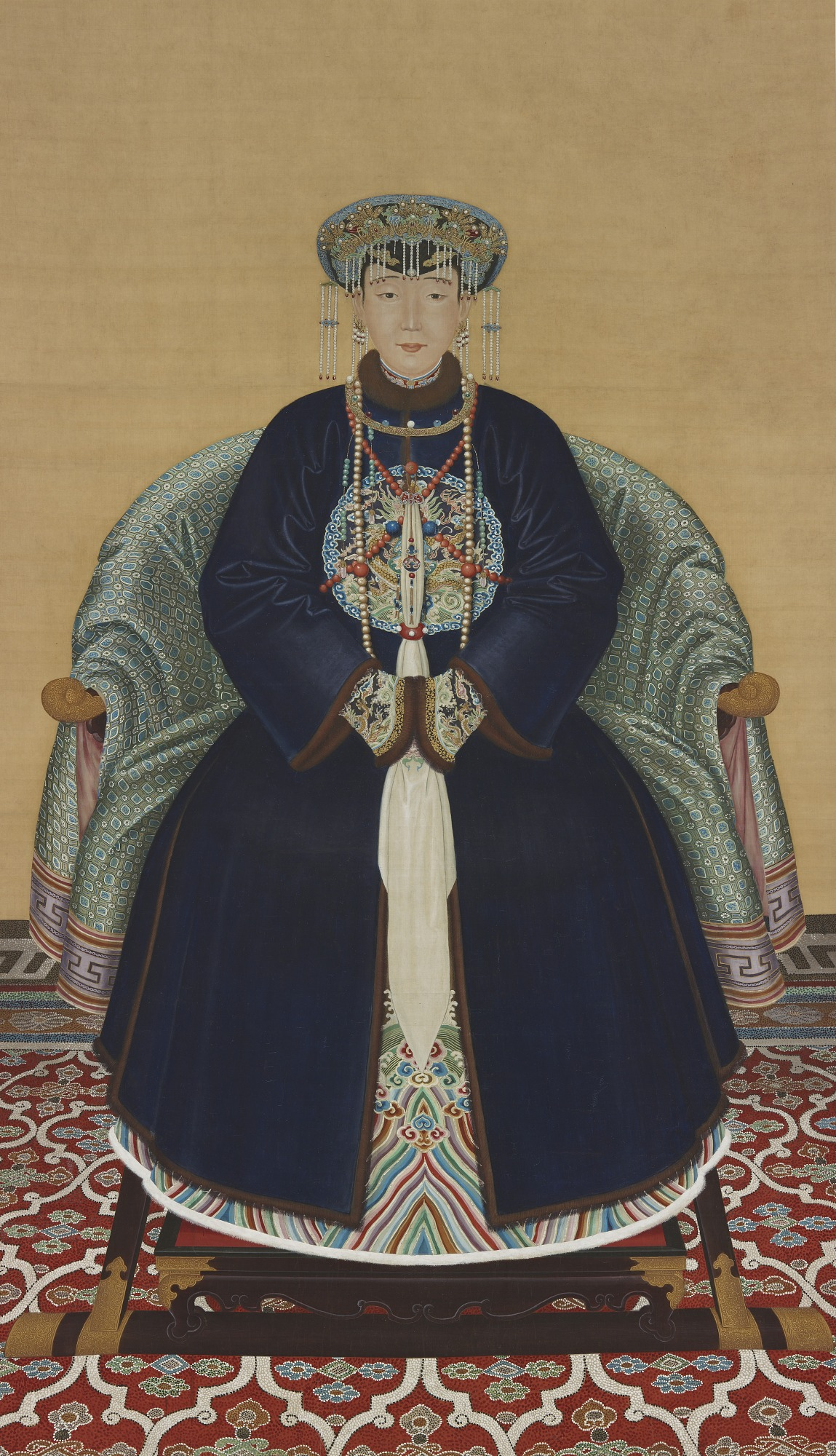 Ancestor portrait of Lady Wanyan, dressed in a blue robe and beaded headdress, seated on a light green fabric draped chair, on top of a red and white patterned carpet