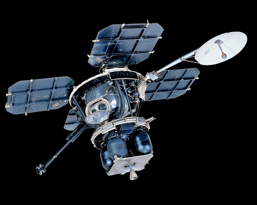 Lunar lander with four square solar panels attached to central instrument box and round satellite dish hanging downward