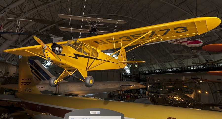 Left front view of yellow monoplane hanging on display in the museum