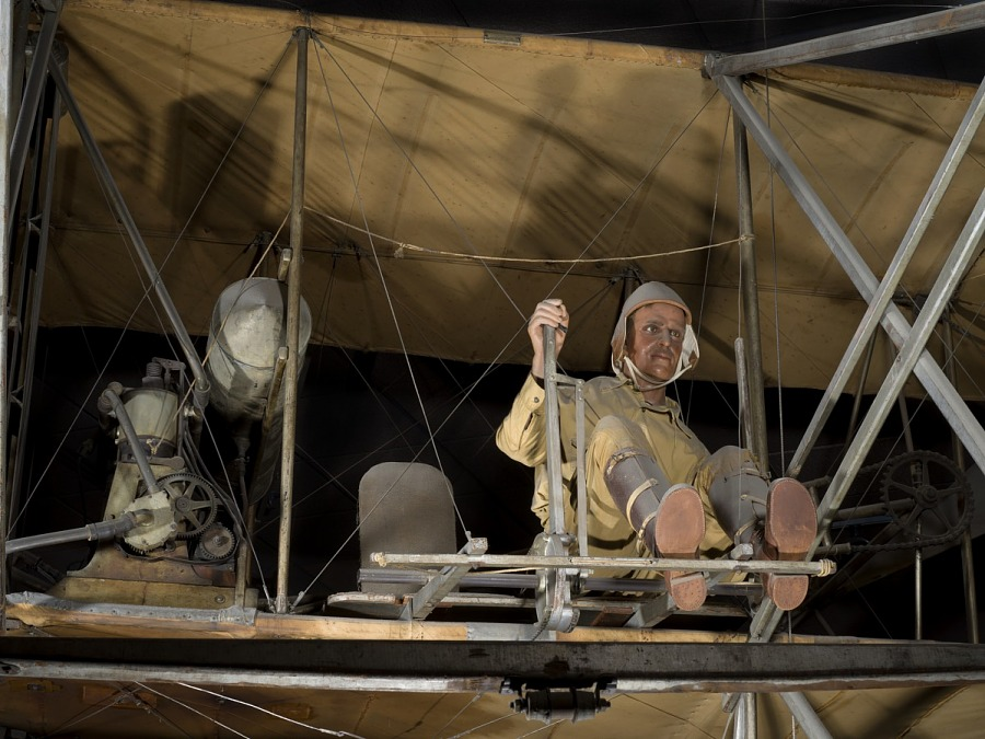 Pilot model in seat of 1909 Wright Military Flyer aircraft next to motor