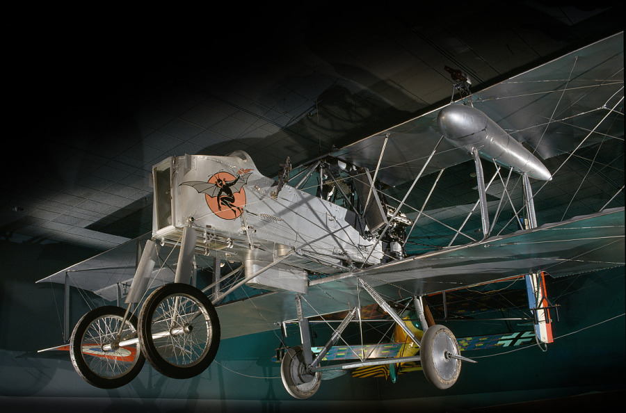 Gray, box-shaped biplane with drawing of winged figure on the nose, shown hanging in museum