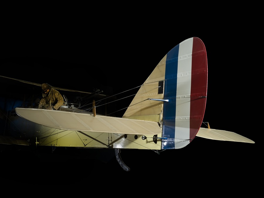 Blue, white, and red striped tail of tan De Havilland DH-4 biplane