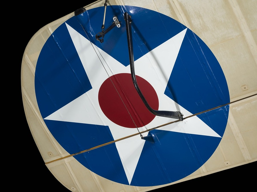 Detail on wing of De Havilland DH-4 aircraft with red circle in center of white star in blue                 circle