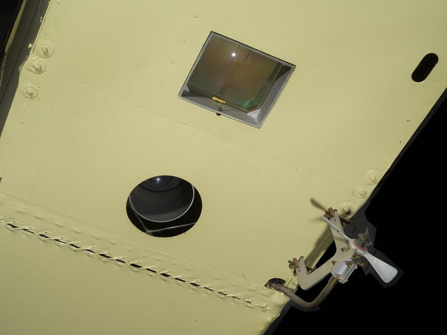 Square-shaped hole and circle-shaped hole on undercarriage of tan De Havilland DH-4 biplane