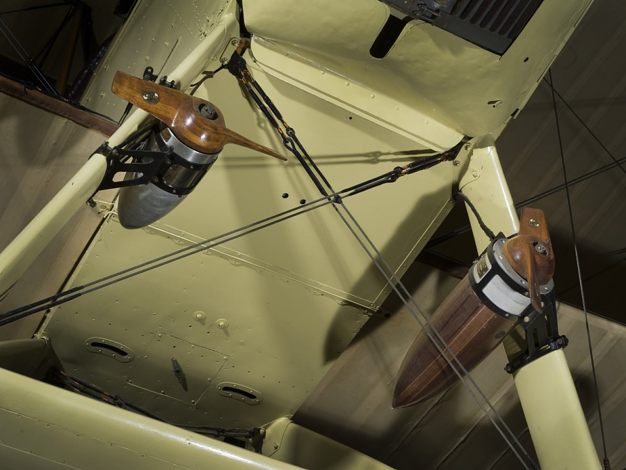 Two wooden bullet-shaped details on undercarriage of tan De Havilland DH-4 biplane