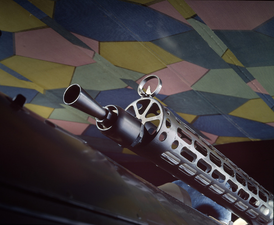Black metal machine gun attached to Fokker D.VII biplane, shown in front of lozenge camouflage                 patterned wings