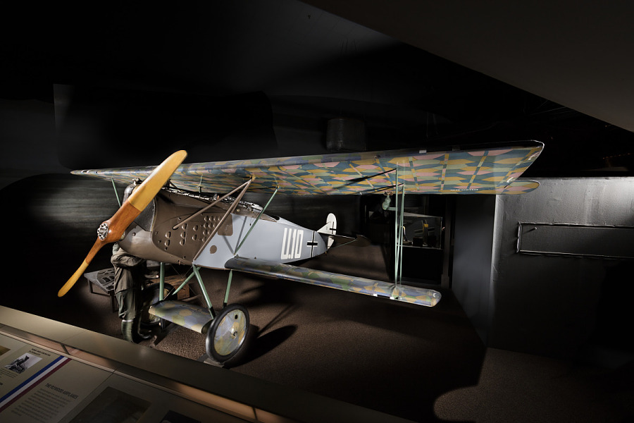 Biplane with multi-color, camouflaged wings, gray fuselage, and olive drab nose, shown on                 exhibit