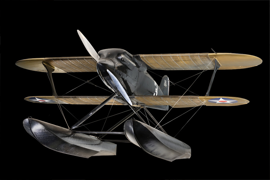 Front of black metal Curtiss R3C-2 biplane with two large spear shaped gliders on bottom of                 aircraft