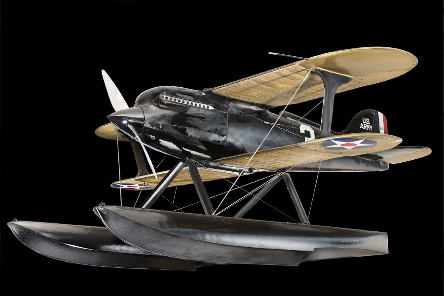 Black metal Curtiss R3C-2 biplane with two large spear shaped gliders on bottom of aircraft