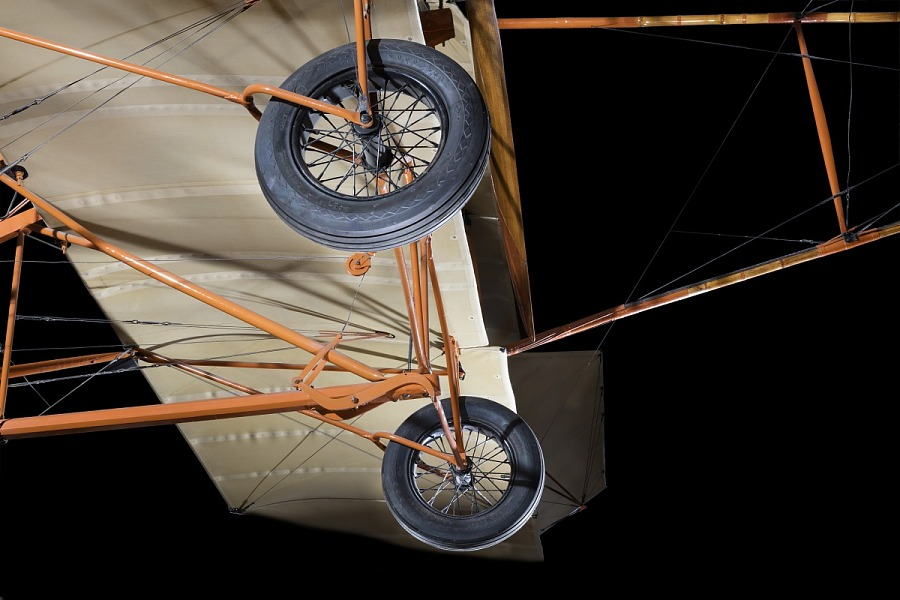Two wheels and orange metal framing of Curtiss D-III Headless aircraft