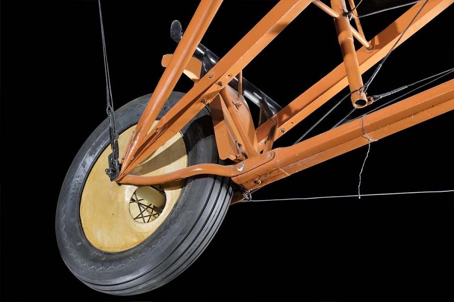 Yellow wheel with tire on orange metal framing of Curtiss D-III Headless aircraft