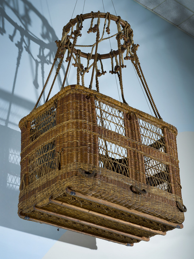 Box-shaped wicker balloon basket with rope hanging in museum