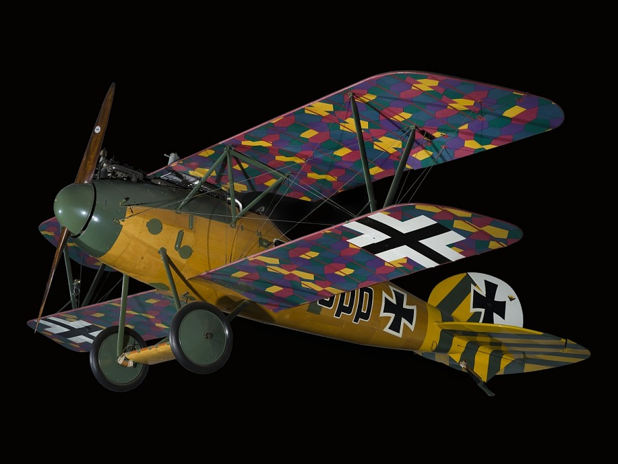 Side view of biplane with multi-color, camouflaged wings, wood grain finish fuselage, and green                 and yellow details on tail and nose