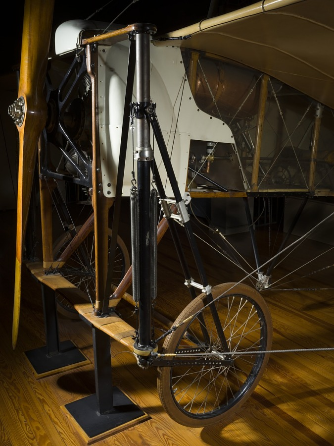 Front of the Bleriot XI aircraft with pistons and front wheels on display stand in museum