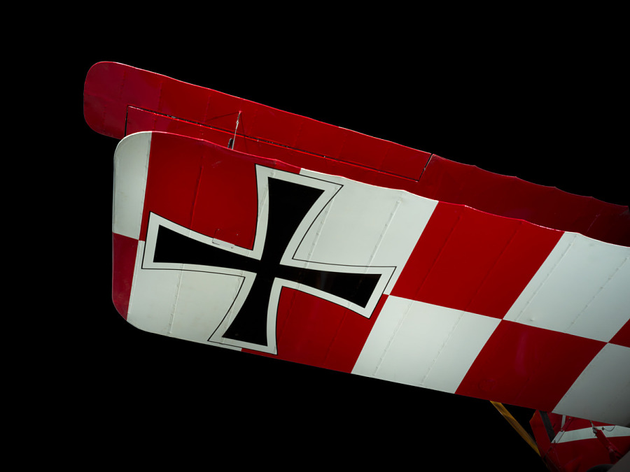 Black cross on bottom of checkered wing of red and white Pfalz D.XII aircraft