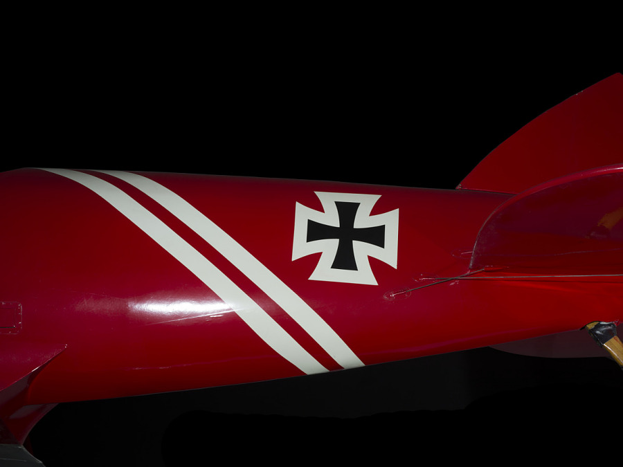 Two white stripes and black cross on body of red and white Pfalz D.XII aircraft