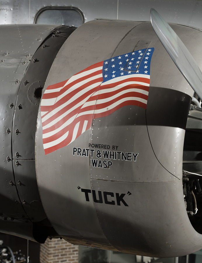 Flipped American flag and 'Tuck' in black lettering on side of engine of gray Boeing 247-D                 aircraft in museum