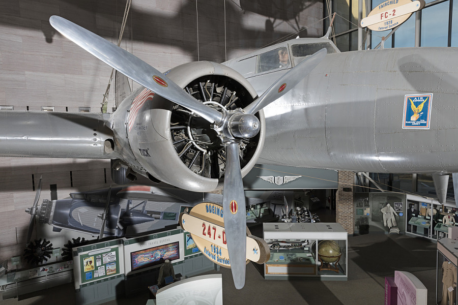 Side engine and tri-blade propeller of gray Boeing 247-D aircraft in museum