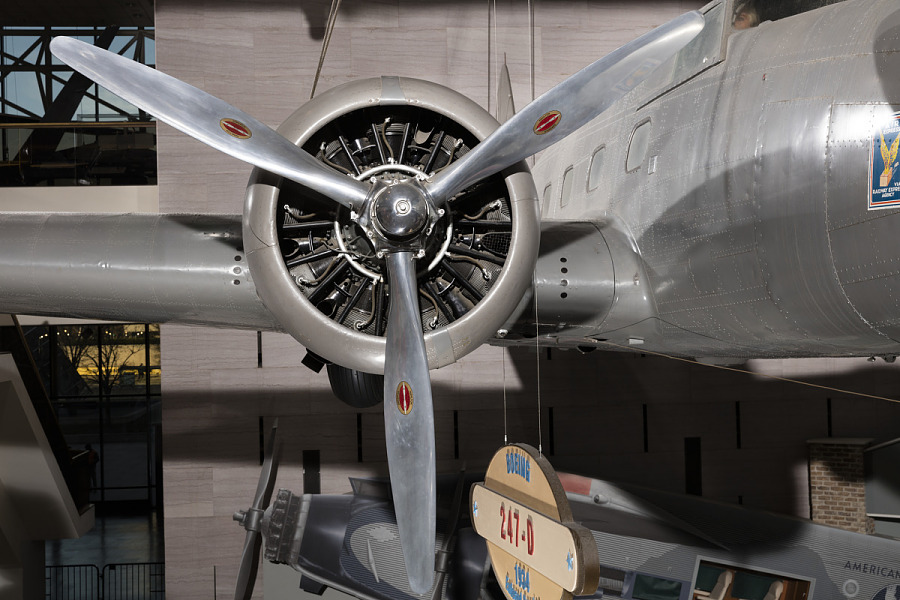 Three-blade propeller and side engine on gray Boeing 247-D aircraft in museum