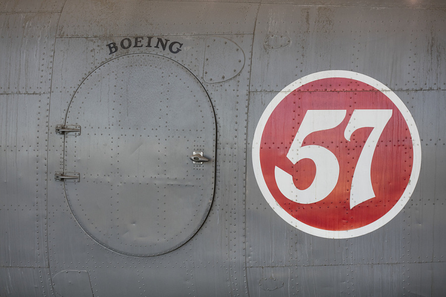 Oval hatch door and '57' in red circle on body of gray Boeing 247-D aircraft