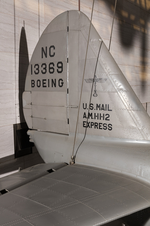 'NC13369 Boeing' and 'U.S. Mail A.M.I.II.12 Express'on vertical stabilizer on gray Boeing 247-D                 aircraft