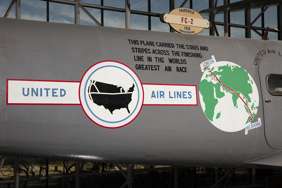 United Air Lines emblem, globe, and record details on side of gray Boeing 247-D aircraft in                 museum