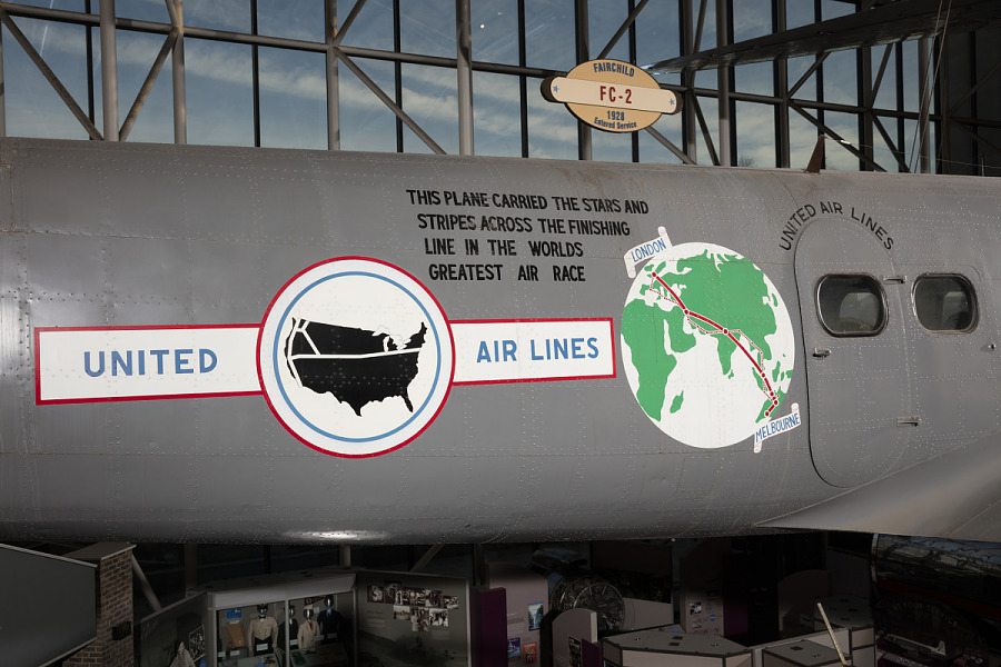 United States Airlines logo, globe, and record details on side of gray Boeing 247-D aircraft in                 museum