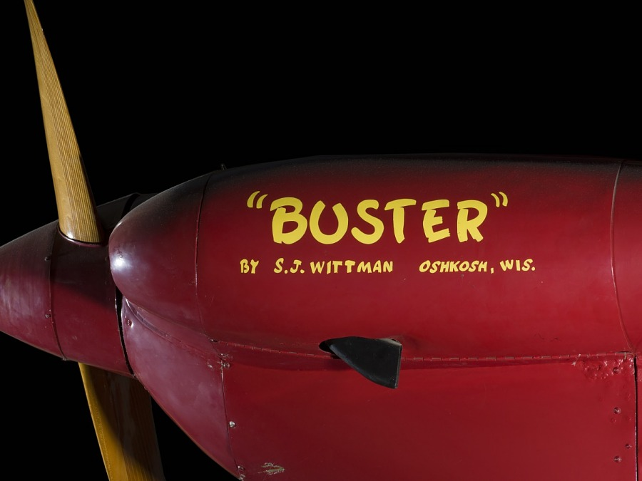 """Side of nose of red Wittman Special 20 """"Buster"""" aircraft with """"""""Buster"""""""" and identification in                 yellow lettering"""