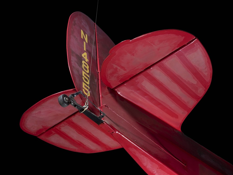 """Tail of red Wittman Special 20 """"Buster"""" aircraft with small rear wheel and """"NI4855"""" in yellow                 lettering"""