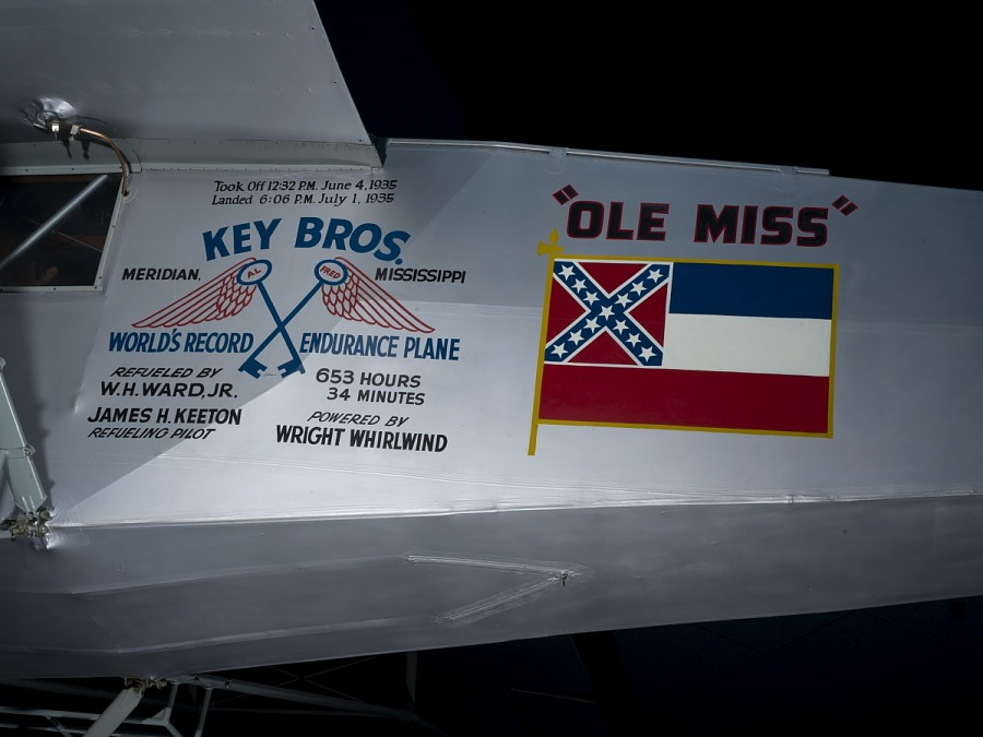 """Insignia for """"Key Bros World's Record Endurance Plane"""" and """"Ole Miss"""" with Mississippi flag and                 details of record flight in black lettering"""