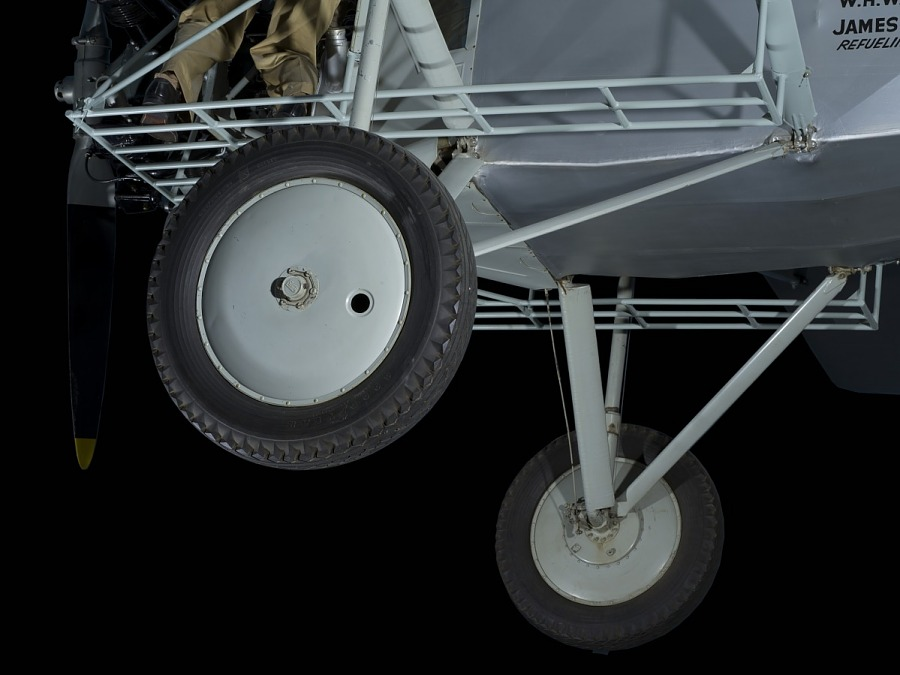 Two wheels and landing gear of gray Curtiss Robin aircraft
