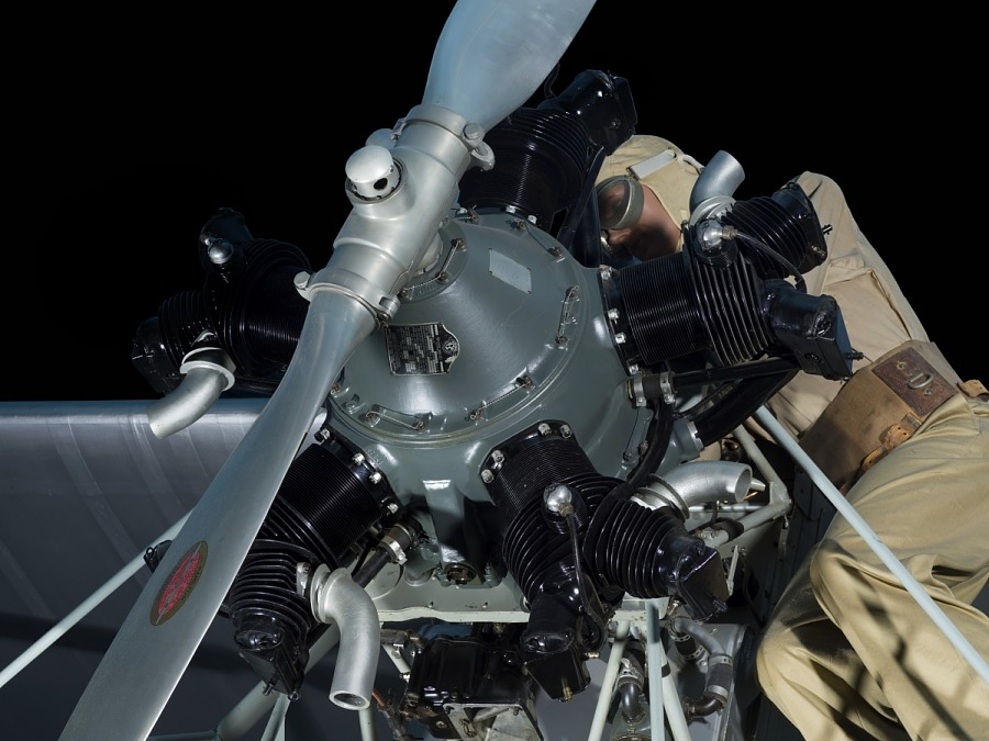 Nose and front rotary engine of gray Curtiss Robin aircraft with model of a man wearing                 goggles