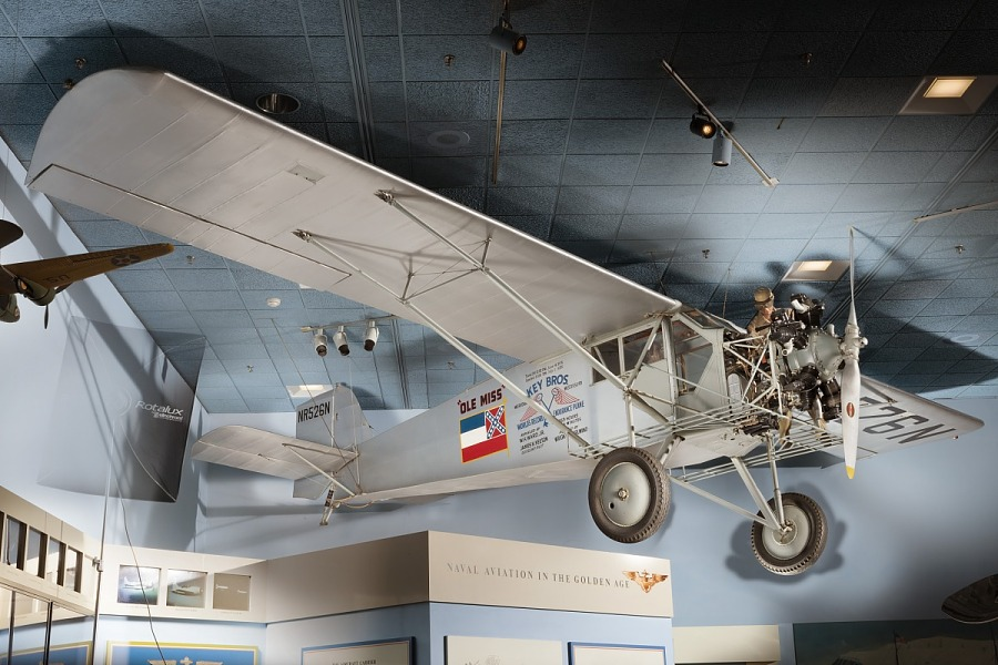 Side of gray Curtiss Robin aircraft hanging in museum with Mississippi flag and 'Ole Miss' in                 black lettering