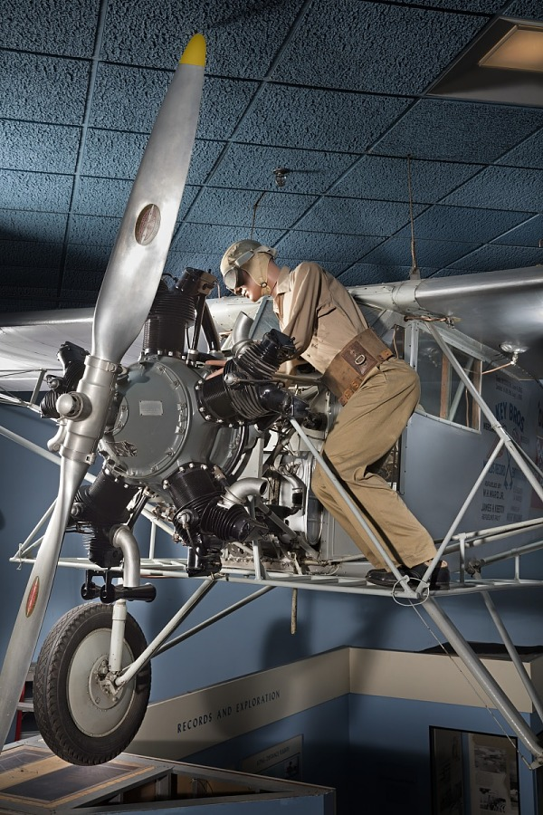 Front cockpit, engine, and landing gear of gray Curtiss Robin aircraft with model of a man                 wearing goggles