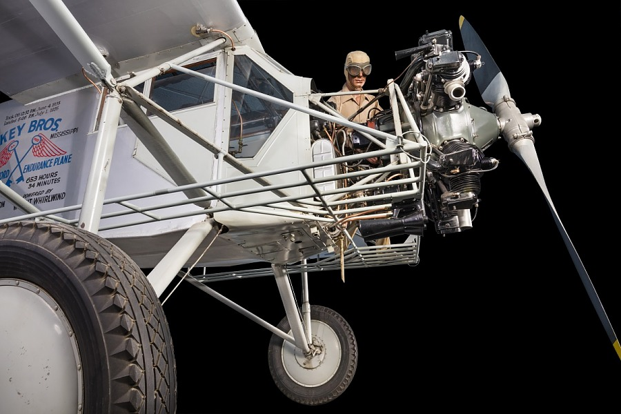 Side view of cockpit, engine, and landing gear of gray Curtiss Robin aircraft with model of a                 man wearing goggles