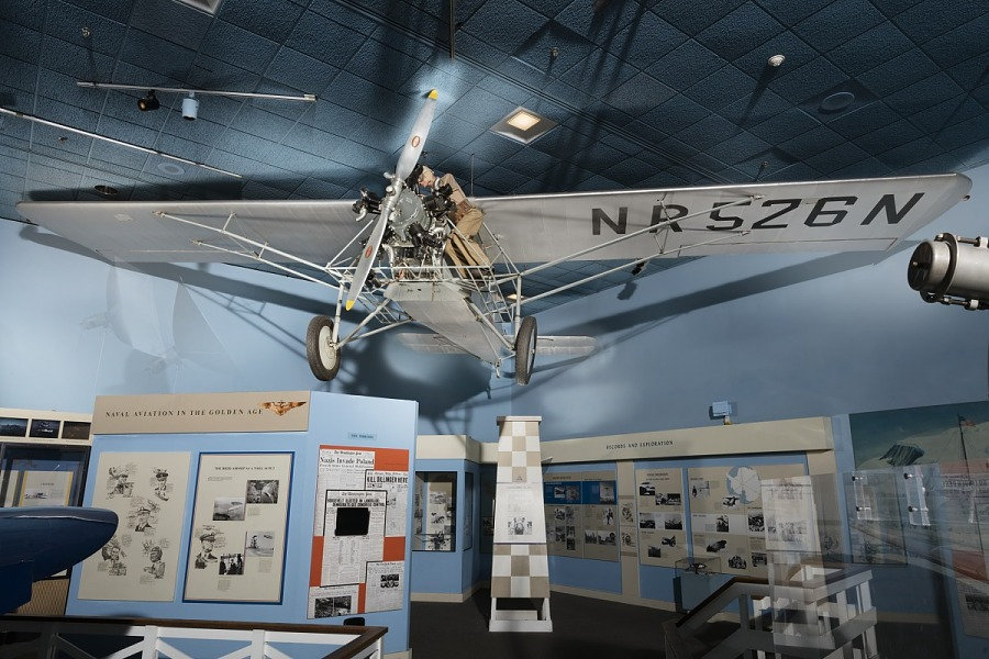 Bottom view of gray Curtiss Robin aircraft hanging in museum