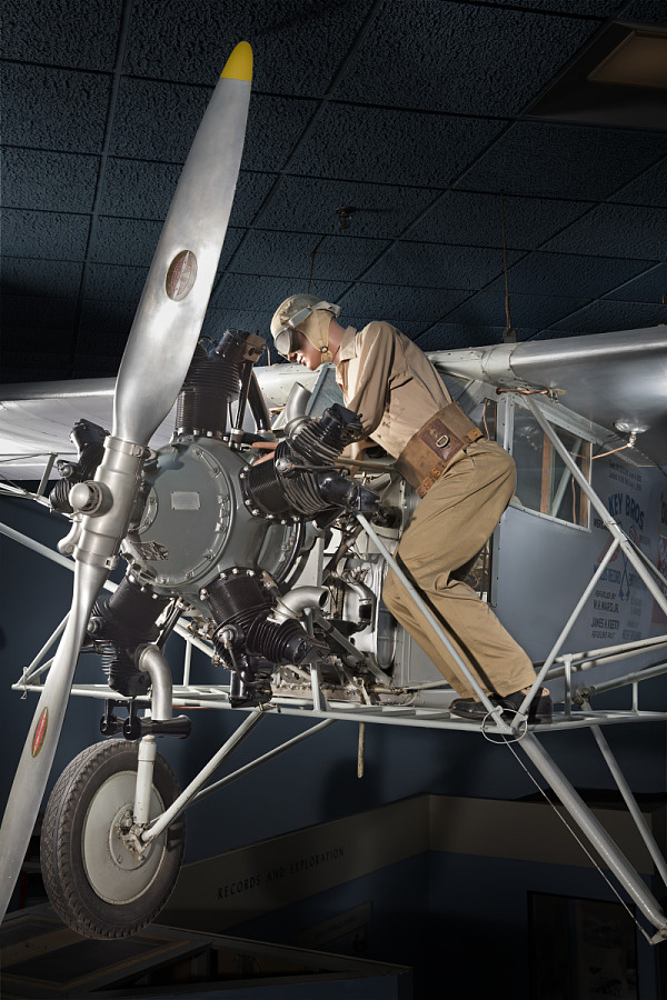 Front cockpit, engine, and landing gear of gray Curtiss Robin aircraft model of a man wearing                 goggles