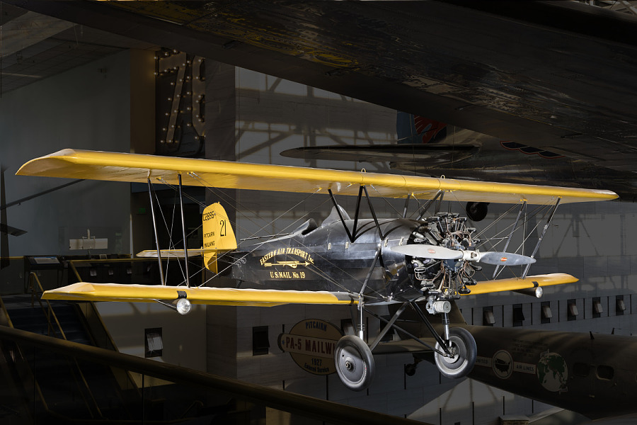 Yellow and black biplane Pitcairn PA-5 Mailwing hanging in museum