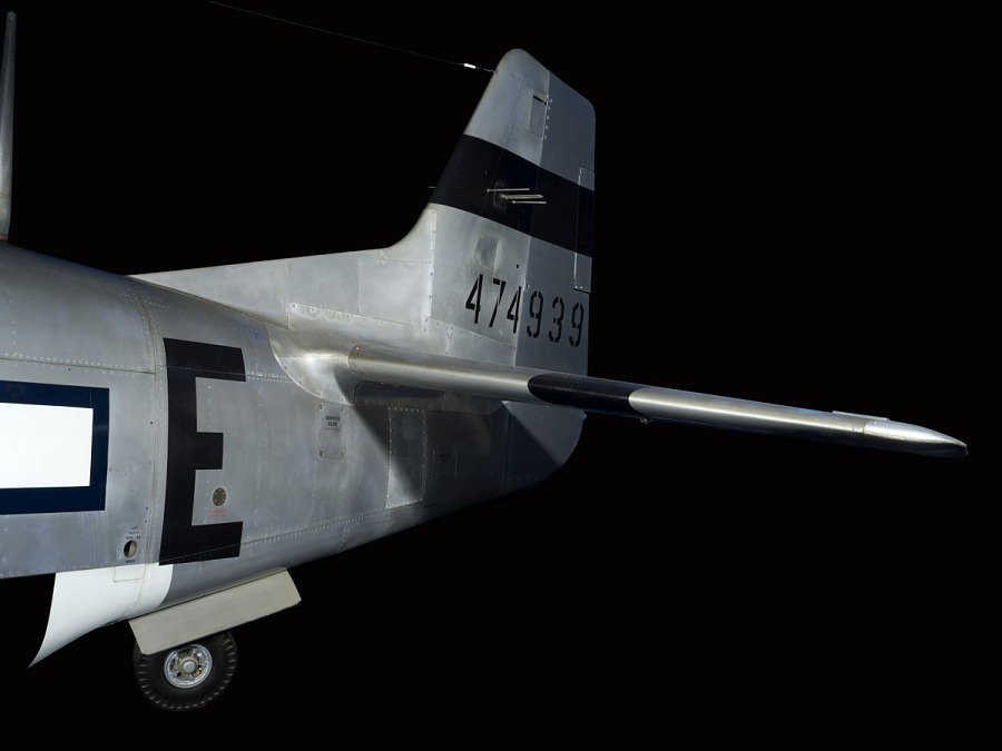 "Tail of P-51 Mustang aircraft with black stripe and ""474939"" in black lettering"