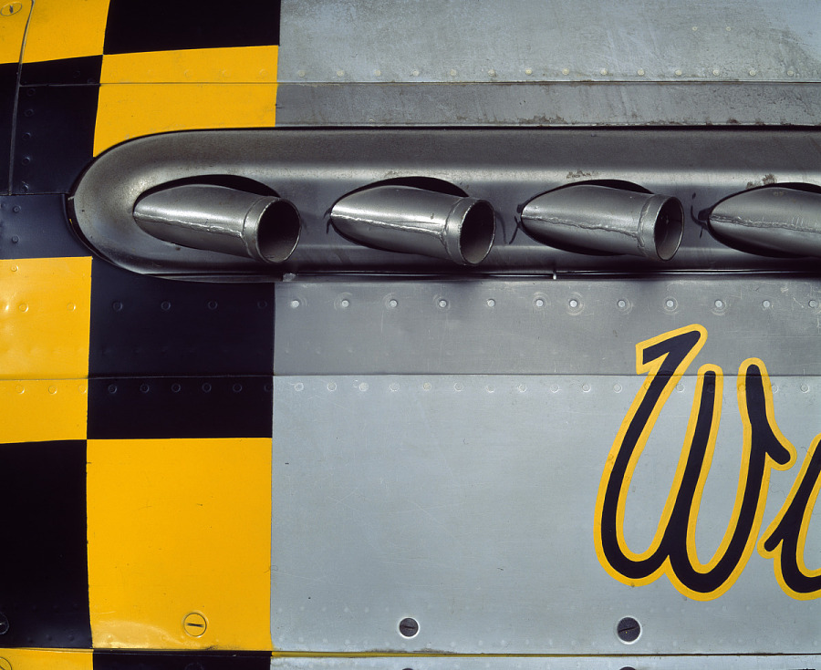 Four exhaust pipes on gray and yellow checkered P-51 Mustang aircraft