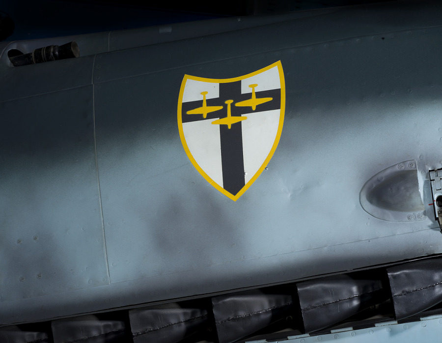 Shield insignia with cross and three downward jets on body of Messerschmitt Bf 109