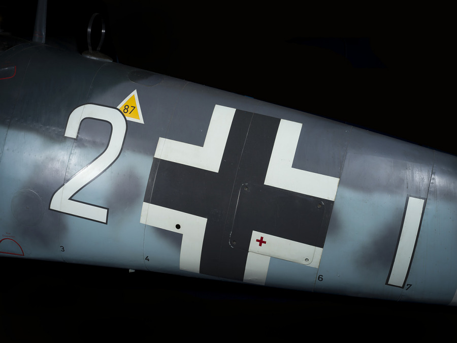 "Body of Messerschmitt Bf 109 aircraft with white and black cross in between ""2"" and ""1"" in white                 lettering"
